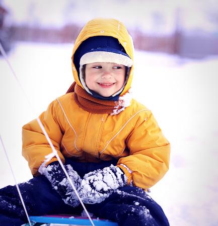 mignonne petite fille: garçon heureux avec traîneau