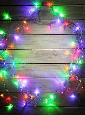 lampada: ghirlande di Natale di lampade su uno sfondo di legno. Telaio di luci di Natale
