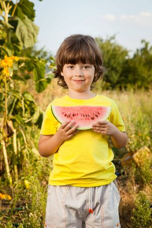 beautiful boys: happy child eating watermelon in the garden Stock Photo