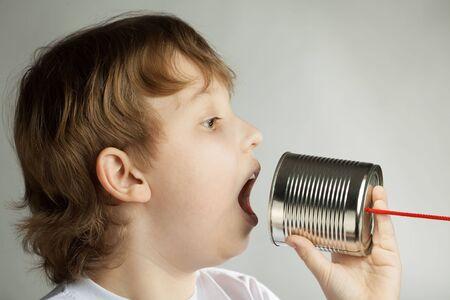 sencillez: ni?o escucha la belleza de lata por tel?fono