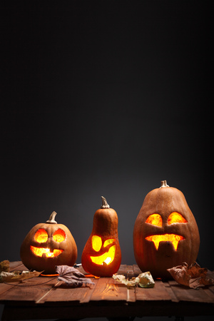 Jack o lanterns Halloween pumpkin face on wooden background and autumn leafs 免版税图像