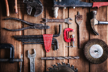 old tools: grungy old tools on a wooden background (processing cross-process)