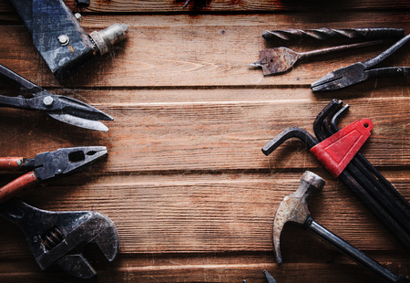 construction workers: grungy old tools on a wooden background (processing cross-process)