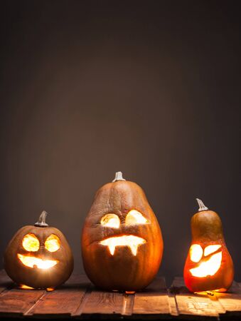 dark backgrounds: Jack o lanterns Halloween pumpkin face on wooden background and autumn leafs Stock Photo