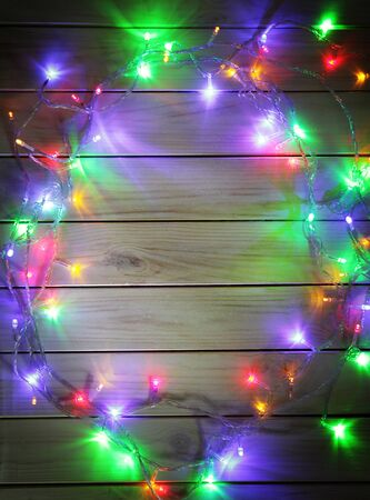 christmas lights background: Christmas garlands of lamps on a wooden background. Frame of Christmas lights