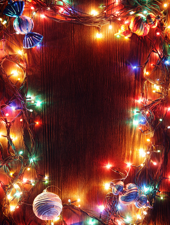 木製の背景のランプのクリスマスの花輪。クリスマス ライトのフレーム