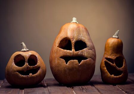 carvings: Jack o lanterns Halloween pumpkin face on wooden background and autumn leafs Stock Photo