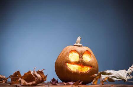 jack fruit: Jack o lanterns Halloween pumpkin face on wooden background and autumn leafs Stock Photo