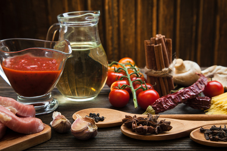 meat food: everything on wood table for the preparation of acute Italian sauce (tomato garlic spices olive oil) Stock Photo