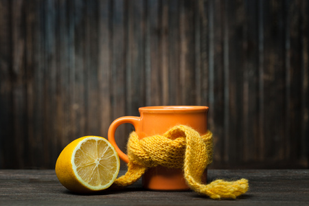 healing: Healing glass of tea in a scarf and a lemon on a wooden background