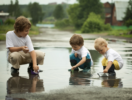 puddle: three boy play in puddle summer day Stock Photo