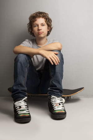 only one teenage boy: happy boy sitting on skateboard