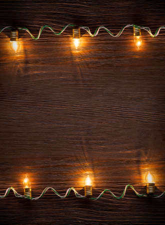 new years background: celebration garland of light bulbs on wooden background copy space for inscriptions