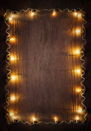 pascuas navideÑas: celebration garland of light bulbs on wooden background copy space for inscriptions