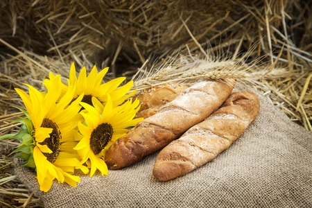 life loaf: ears of wheat and bread lay on sackcloth in the haystack
