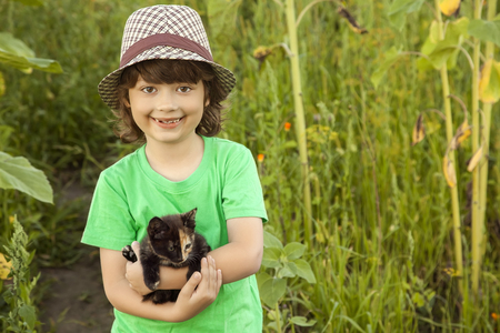 affectionate: Happy kid with a kitten in her arms in nature