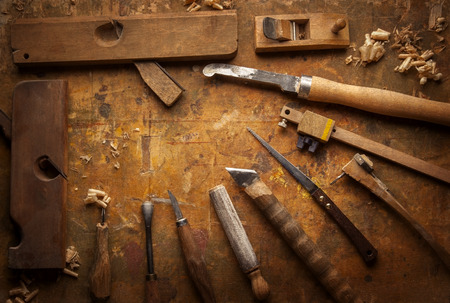 carvings: Hand tools Wood (Drill Jig Saw plane chisel) on an old wooden workbench