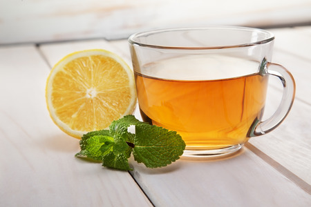 mint: cup of tea, mint and lemon on a wooden table