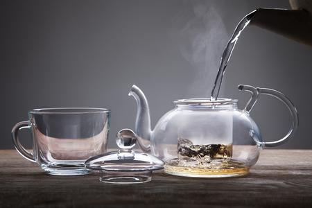 木製テーブルの上に紅茶のティーポット カップから注がれる