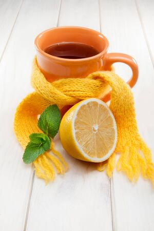 illness: Healing glass of tea in a scarf on a wooden background