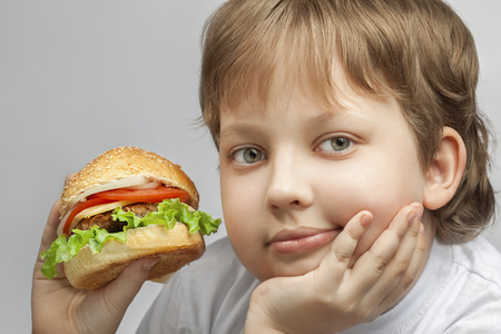 eating fast food: happy boy with burger