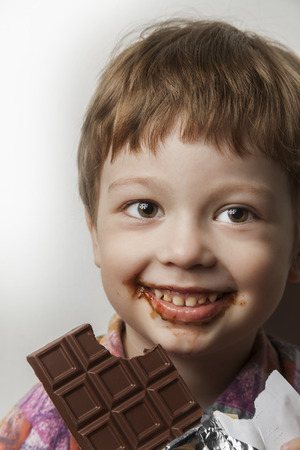 child laughing: happy boy with chocolate bar