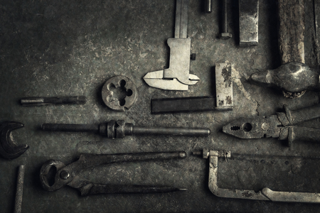 grungy old metalwork tools on stained table background (processing cross-process)