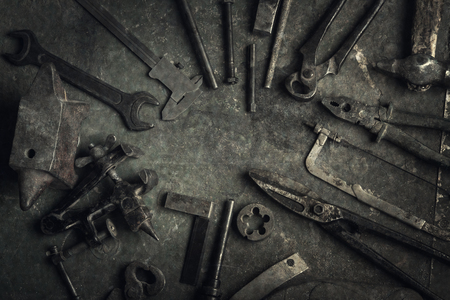 metalwork: grungy old metalwork tools on stained table background (processing cross-process) Stock Photo