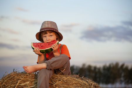 children eating: boy eating watermelon on a haystack