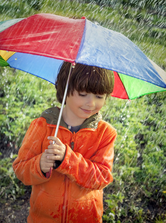 2 persons only: happy boy with umbrella outdoors Stock Photo