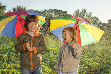 2 persons only: two happy brother with umbrella outdoors