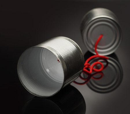 comunicação: telefone de brinquedo de uma lata deitado sobre uma mesa polida preta lisa Banco de Imagens