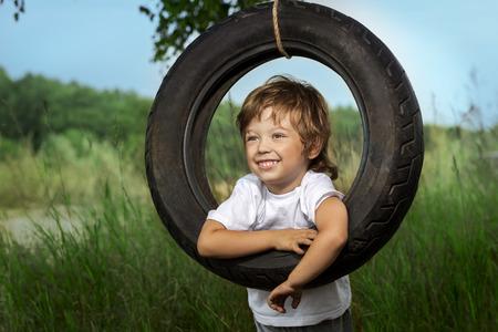 happy smile: happy boy on swing outdoors Stock Photo
