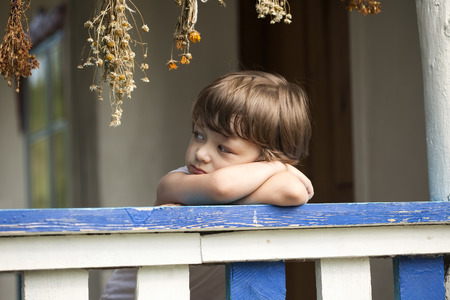boys only: sad little boy on the porch of rural house