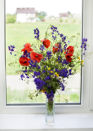 Bouquet of wildflowers on a plastic window