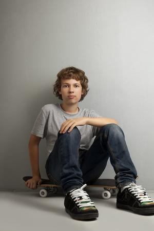 one boy only: happy boy sitting on skateboard