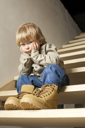 big shoes: Big shoes to fill, childs feet in large shoe