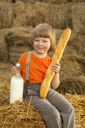 non urban 1: child on a haystack with bread and milk