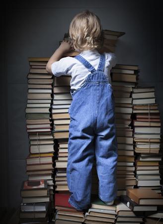 persona leyendo: niños alcanzan para un libro Foto de archivo