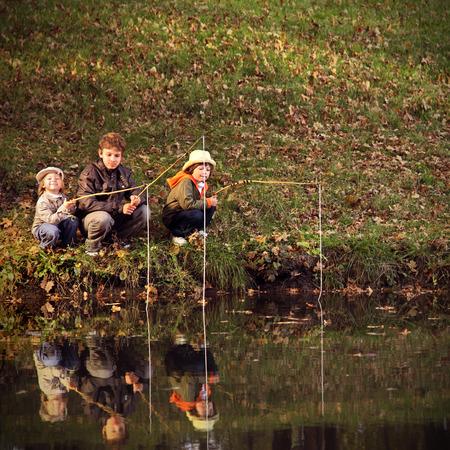 niños sentados: felices los niños van a pescar en el río
