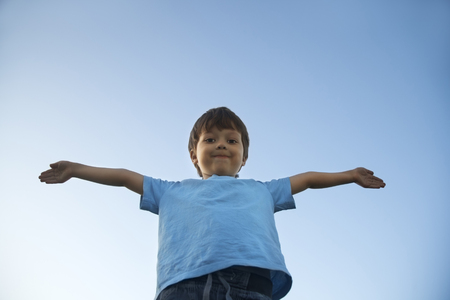 arms up: boy with widely placed hands on background of the sky