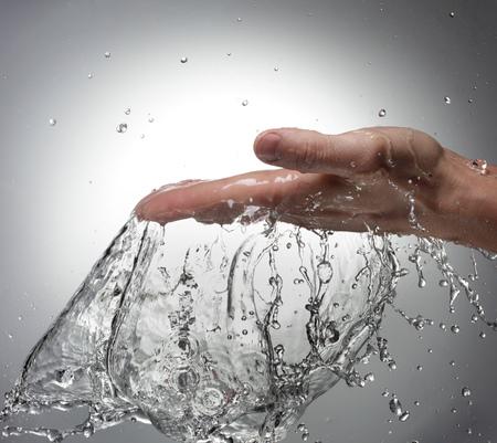 hand water: Splash of Water in Woman Hand Stock Photo