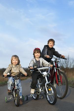 boys playing: three brothers ride bikes