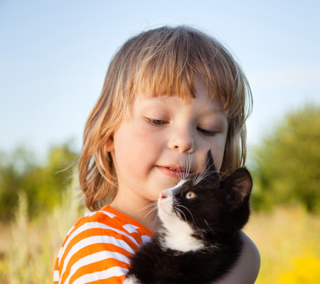 feelings and emotions: Happy kid with a kitten in her arms in nature