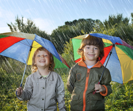 two persons only: two happy brother with umbrella outdoors