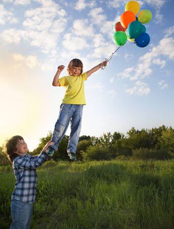 hermanos jugando: dos hermanos que juegan - uno vuela en los globos otra sostiene (fotomontaje)