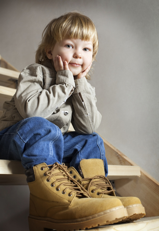 big shoes: Big shoes to fill, childs feet in the large shoe