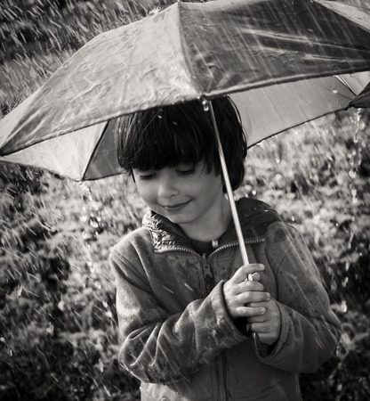 two persons only: happy boy with umbrella outdoors Stock Photo