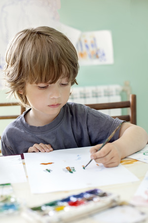 one room school house: Children draw in home with watercolor and brush Stock Photo