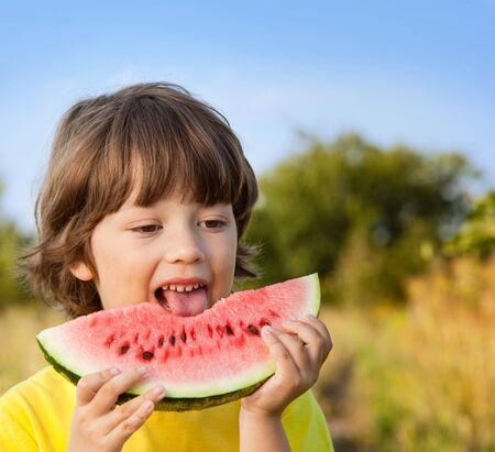 eating fruits: happy child eating watermelon in the garden Stock Photo